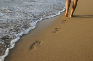 legs walking barefoot in the sand next to the beach shoreline