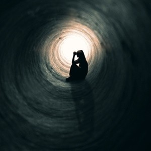 woman alone in pain sitting in tunnel praying