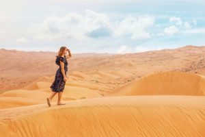 Woman Searching (for a Functional Medicine Approach) While Walking on the Sand